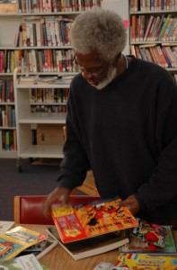 "Calvin J. Bush straightens up some reading material at the Martin Luther King Jr. Reading and Cultural Center, located in Pittsburgh's Hill District, on November 11, 2009. Bush has been volunteering his time as the center's Technology and Education specialist since 2007. ""I'm not able to collect a paycheck right now, but if I wasn't here where would these children go?"" said Bush. By Andrew Weier, Point Park News Service"